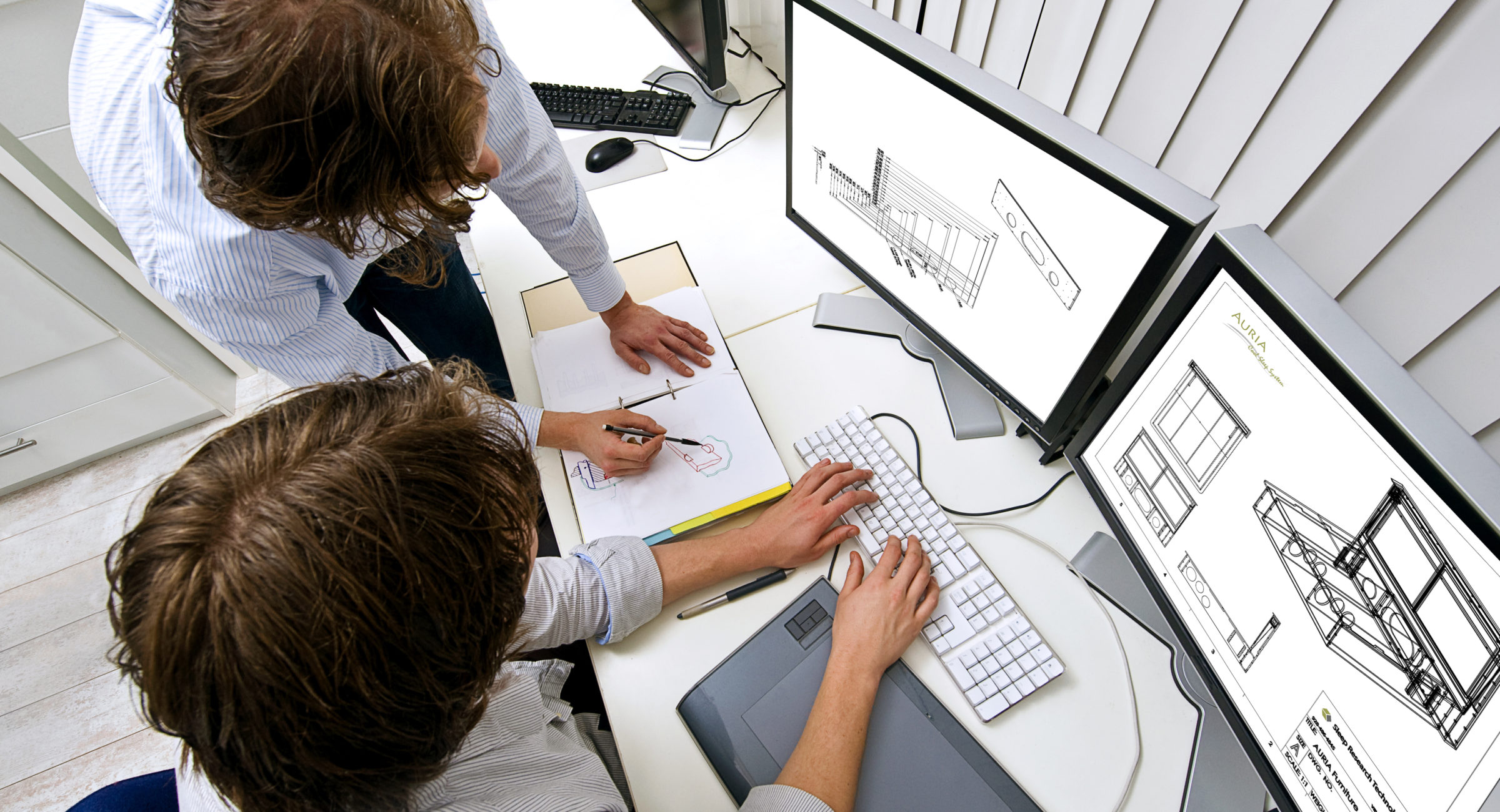 Two engineers, working together in an office, one explaining something to the other